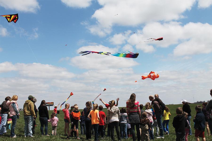 People flying kites in an open field in Iowa.