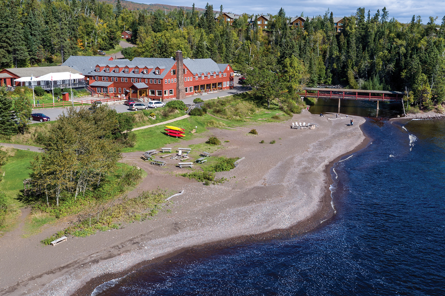 An aerial shot of Lutsen Resort shows a large red building surrounded by a forest and lake in northern Minnesota.