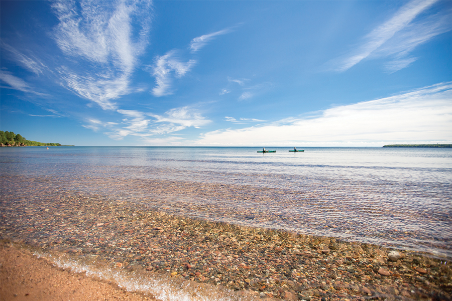 A shoreline with crystal clear water blanketing rocks in Madeline Island, Wisconsin.