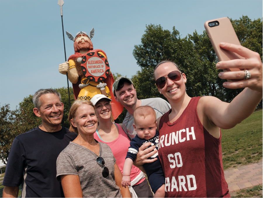 People taking a selfie in front of Big Ole in Alexandria, MN.