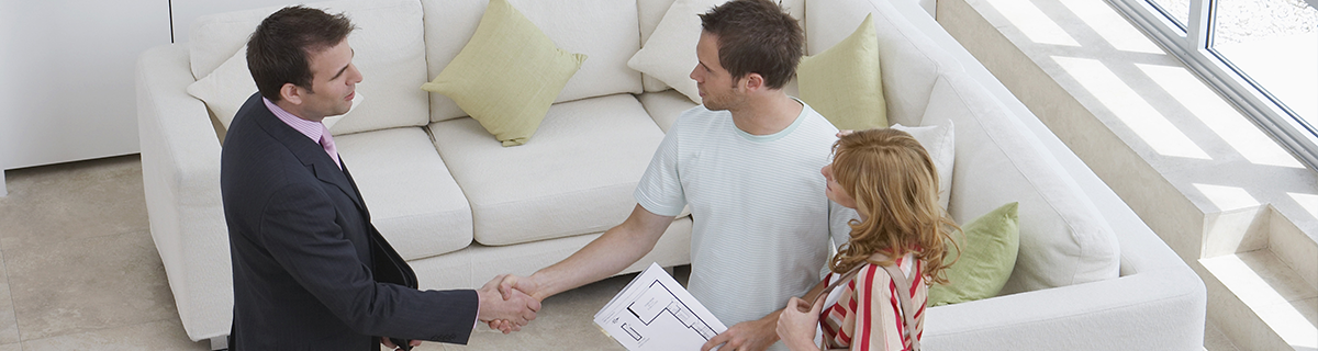a man and a woman in a living room, the man shaking hands with a real estate agent