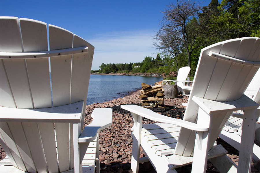 Two chairs sit next to a fire ring on the shore of Lake Superior prepped for Glensheen Mansion bonfire nights.