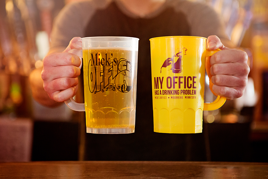 A person holding two mugs of beer at Mick's Office.