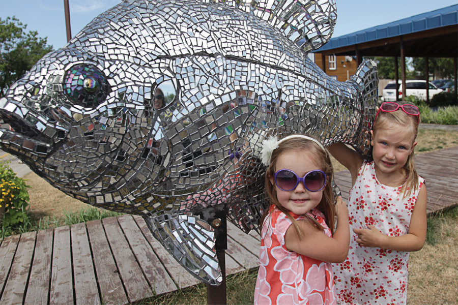 Two little girls posing by a metallic sunfish sculpture in Detroit Lakes, MN.