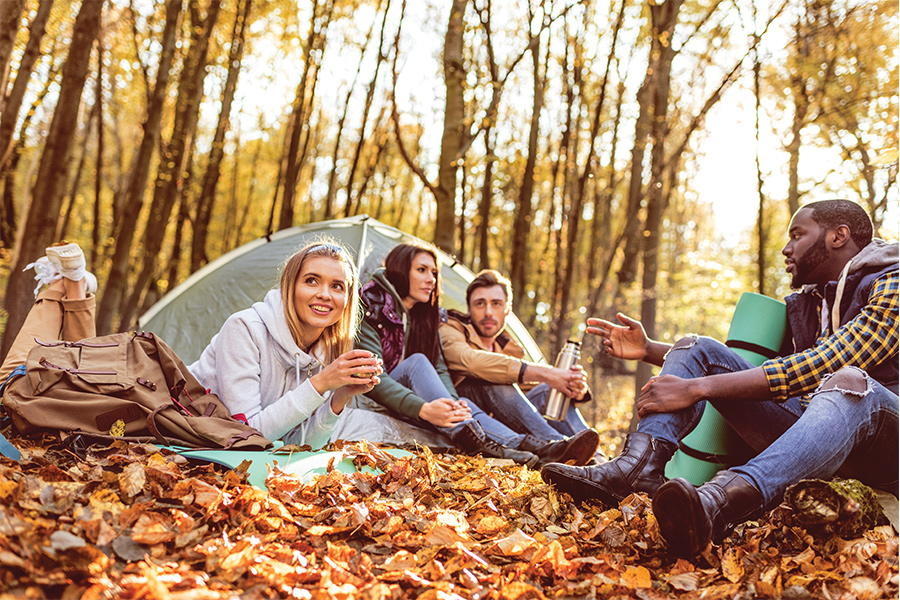 A group of people sitting in leaves next to a tent during some fall camping.