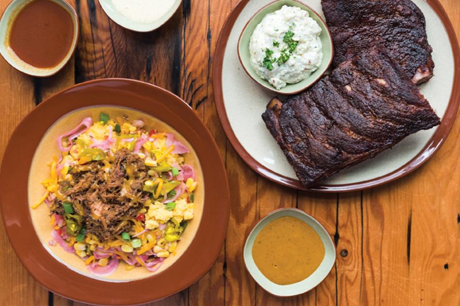 OMC Smokehouse's pork n' grits and ribs with potato salad.