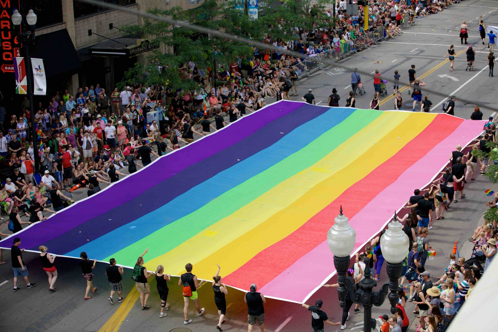 A photo of the Twin Cities Pride parade in 2015. A huge rainbow flag is stretched out across the street, held by dozens of marchers. Photo by RJL Photography.