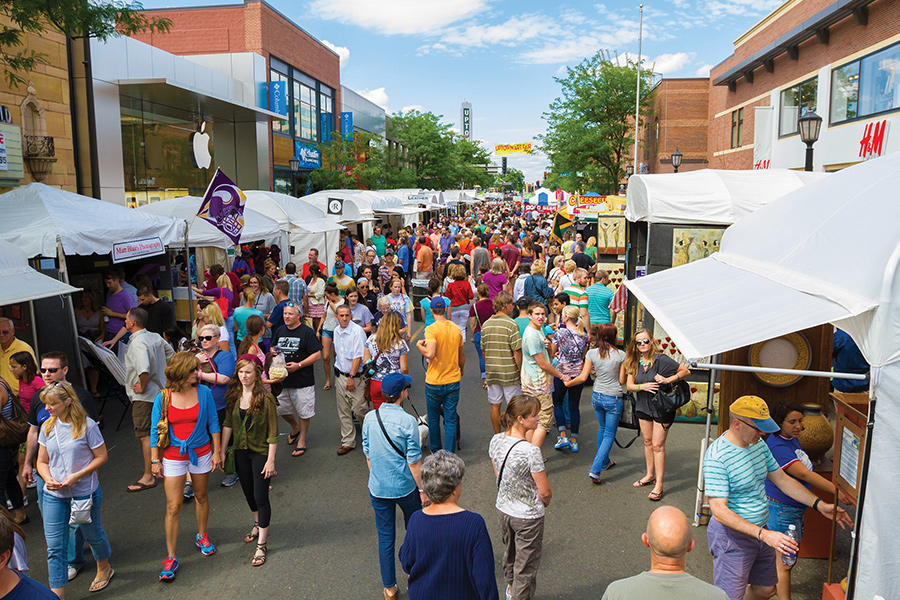 People attending the Uptown Art Fair in Minneapolis, Minnesota on a sunny day.