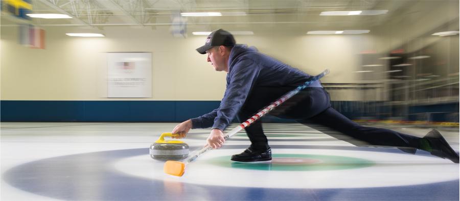 Olympic curler John Shuster mid toss during curling.