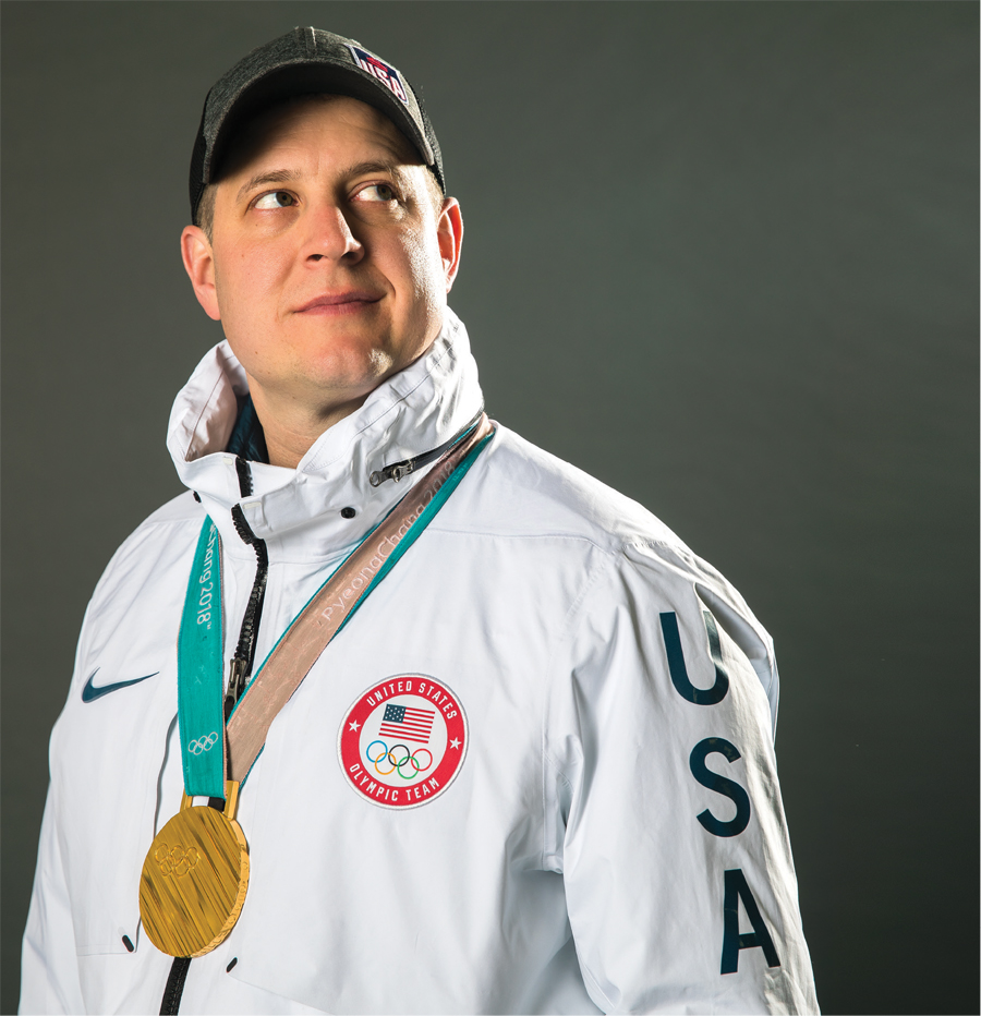 A portrait of Olympic curling champ John Shuster wearing his gold medal.