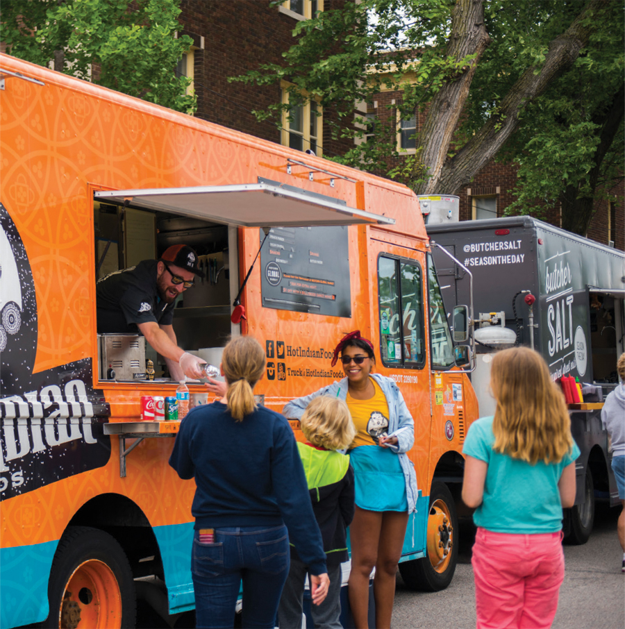 People waiting in line at an orange food truck during the Uptown Food Truck Festival.
