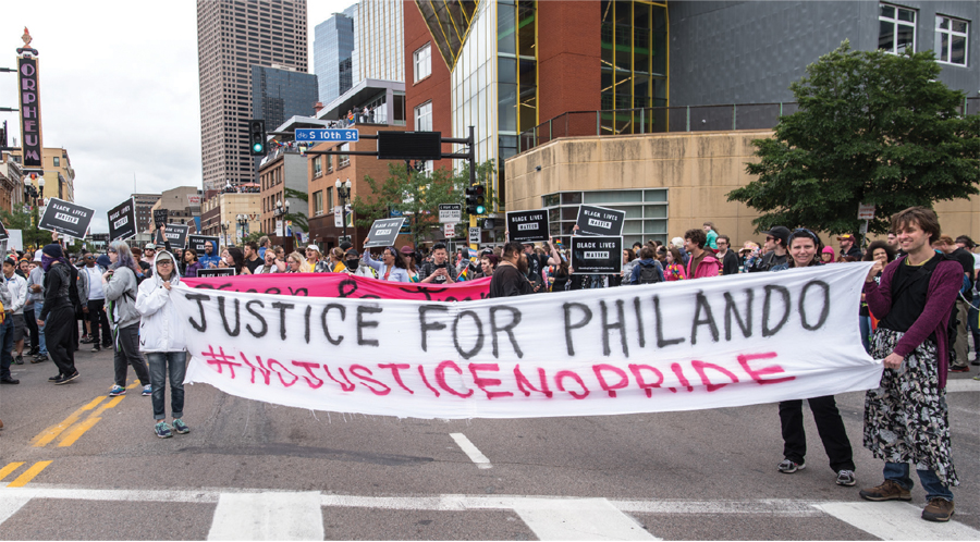 """People holding a banner reading """"Justice for Philando"""" during the Twin Cities Pride parade."""