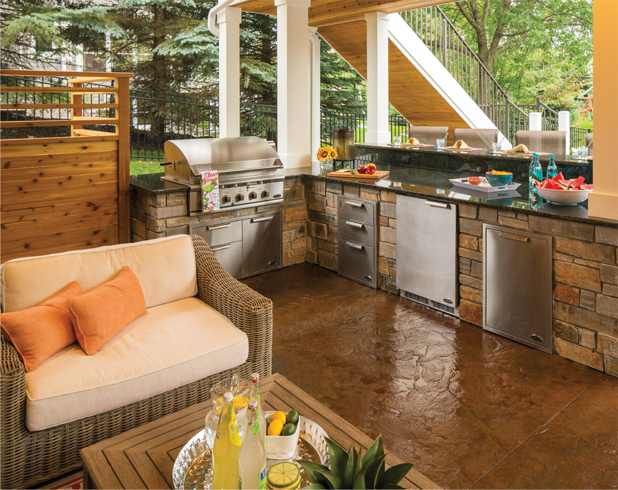 An outdoor kitchen complete with stainless-steel appliances built into Fond du Lac stone and granite top counters.