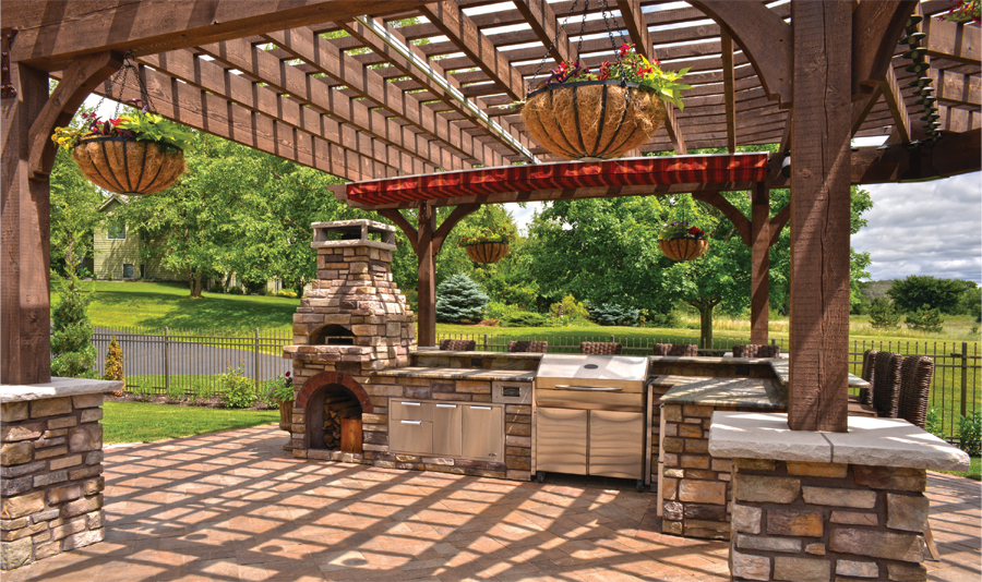 A pergola looms over a built-in stone pizza oven in a backyard.