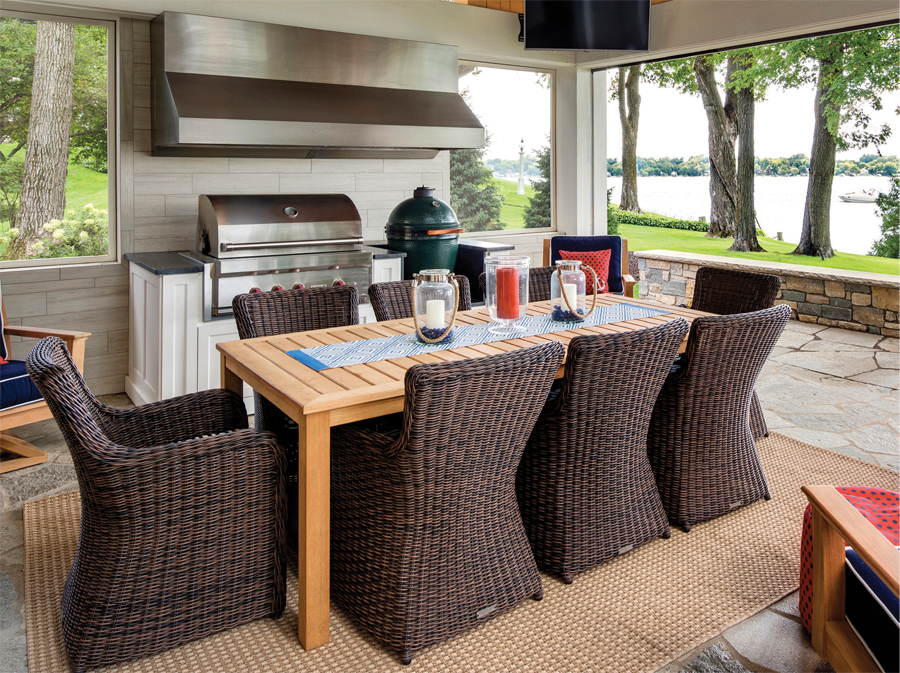 Wicker chairs surround a table next to an outdoor grill.