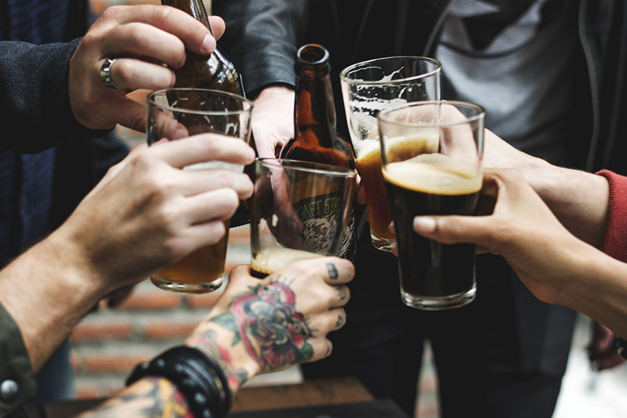 A group of people cheers'ing with glasses and bottles of beer.