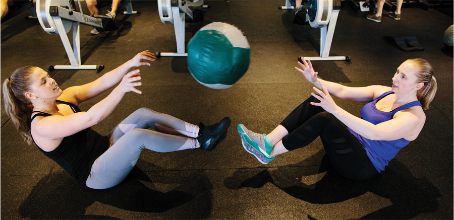 Two girls passing a medicine ball back and forth at Twin Town Fitness.