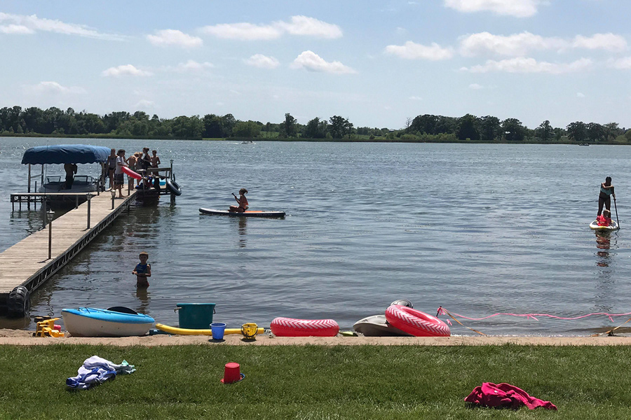 People playing on a dock and in the water at Lake Sarah.