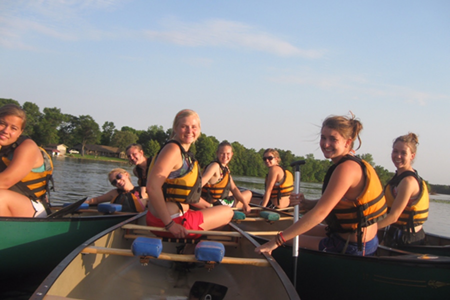 A group of girls canoeing.