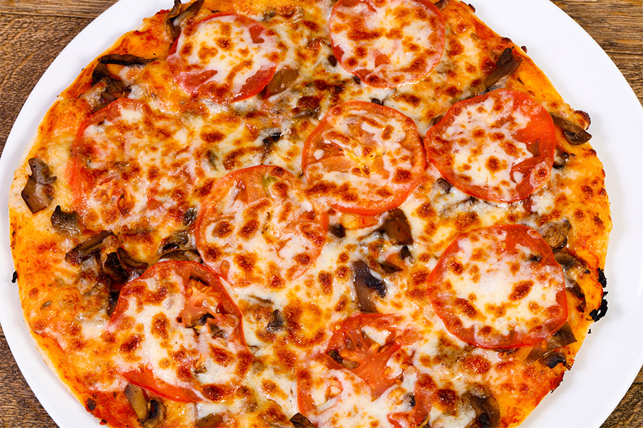 A close up of a pepperoni and mushroom pizza.