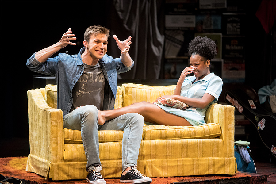 A boy and girl sitting on a couch in a production of The Legend of Georgia McBride.