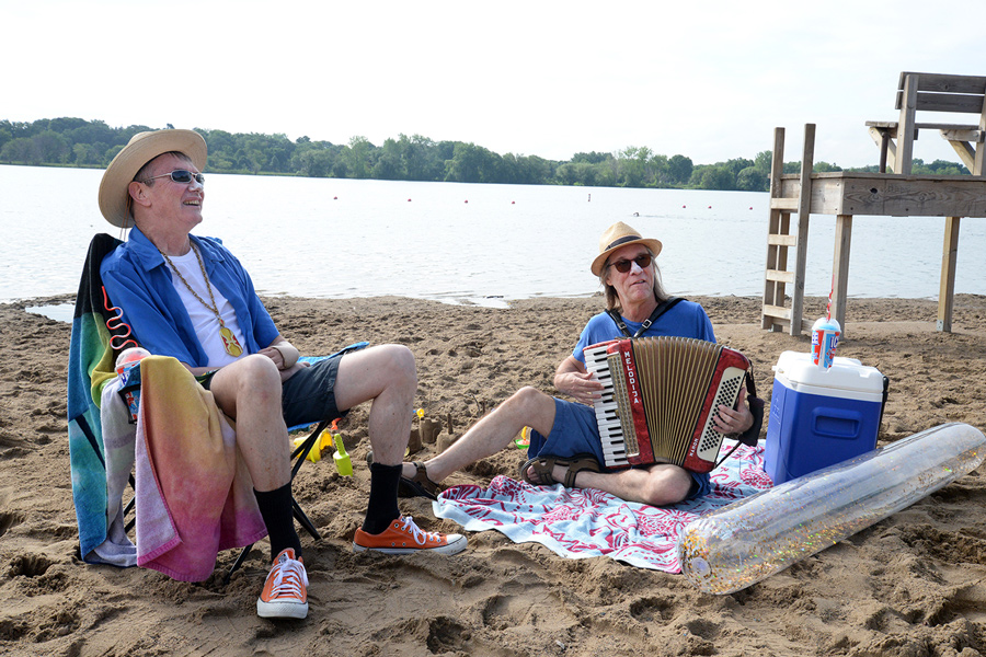 Two guys sitting on the beach. One is playing an accordion.