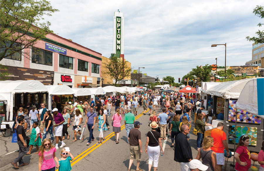 People walking the streets at the Uptown Art Fair.