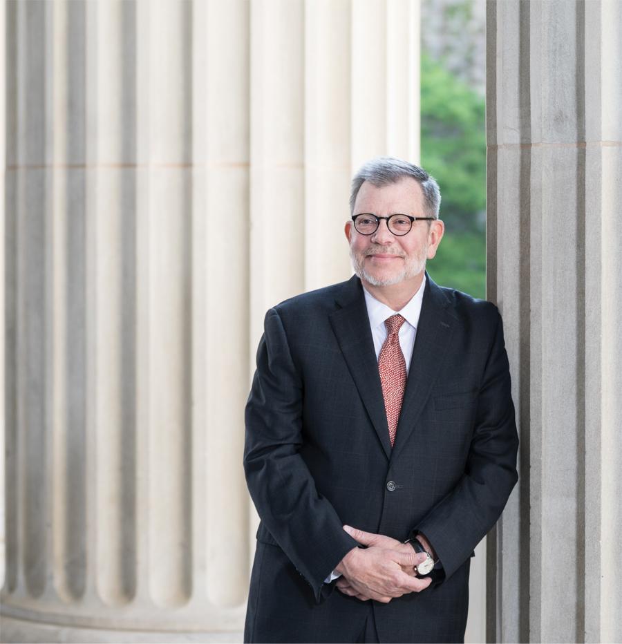 A portrait of University of Minnesota President Eric Kaler leaning against a pillar.