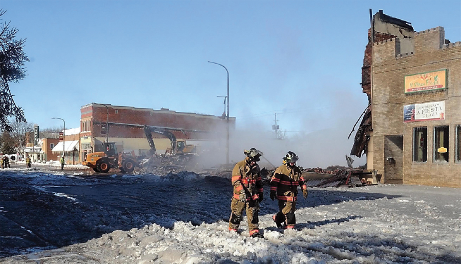 Two firefighters walk through rubble of a demolished building.