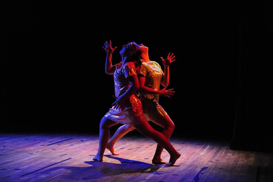 Two people dancing in a dark room in a performance of Rhythmically Speaking.