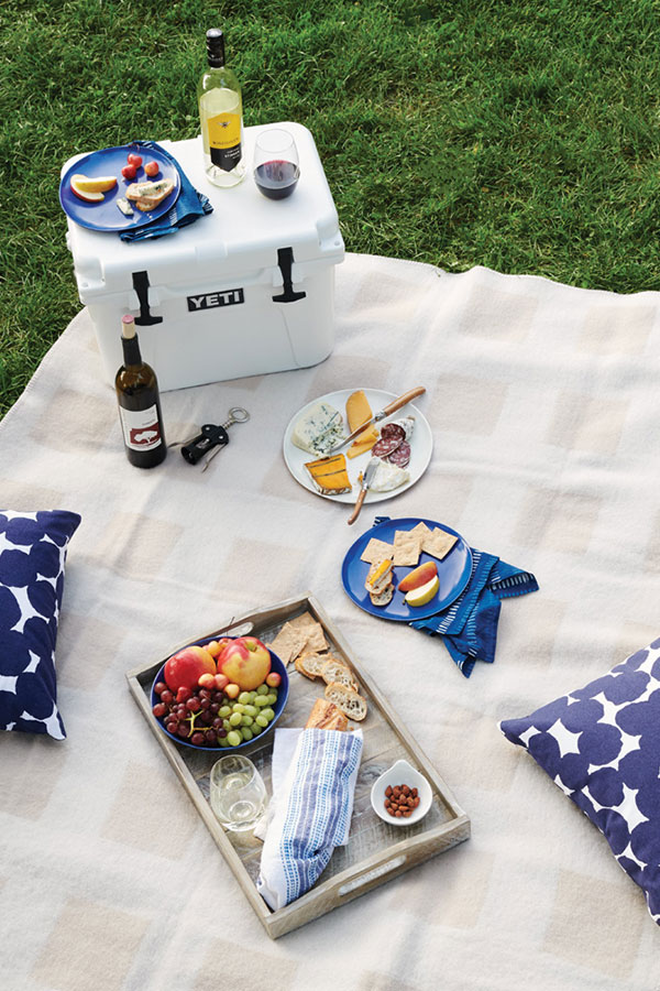 A picnic set up with wine, food, and pillows.