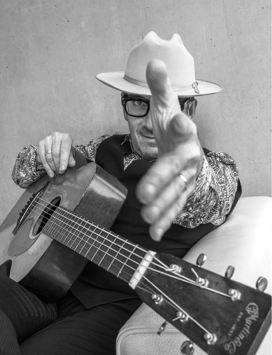 A black and white portrait of Elvis Costello and the Imposters.