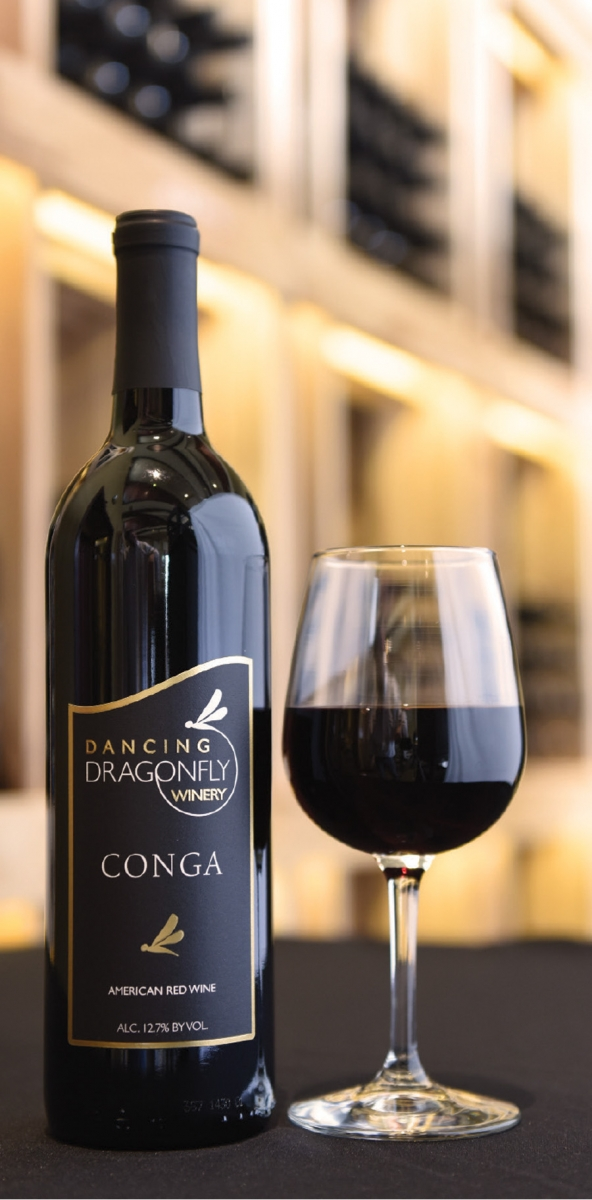 A bottle of wine and a glass at Dancing Dragonfly Winery.