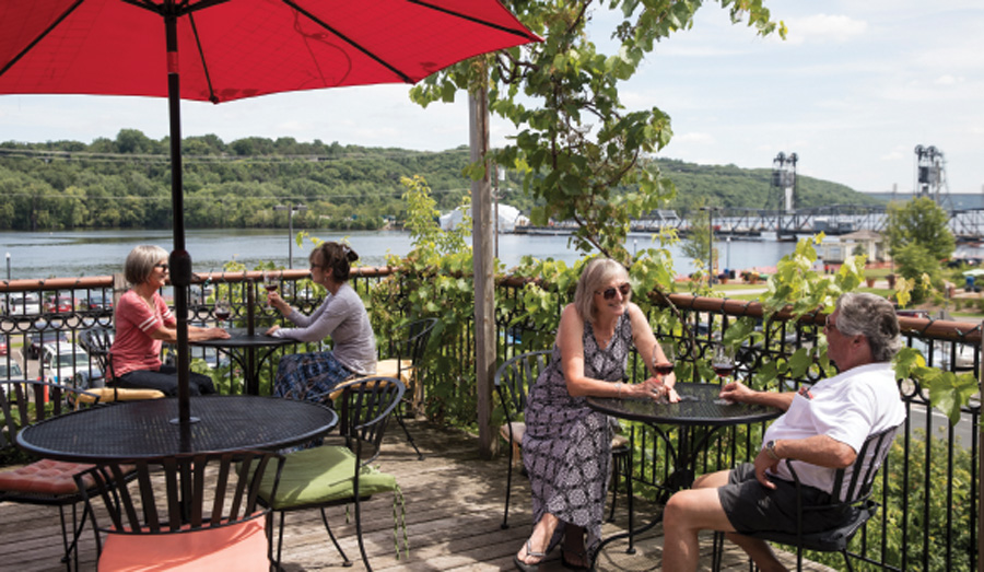 People sitting on the patio at Northern Vineyards Winery in Stillwater, Minnesota.