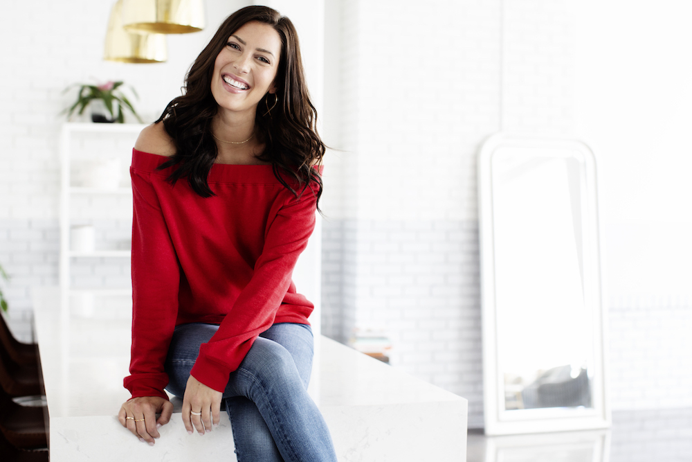 A portrait of Becca Kufrin sitting on a kitchen island in a red shirt and jeans.
