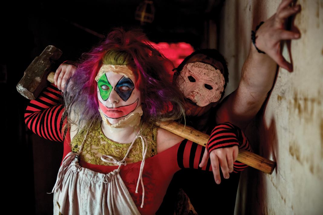A clown holding a sledgehammer.