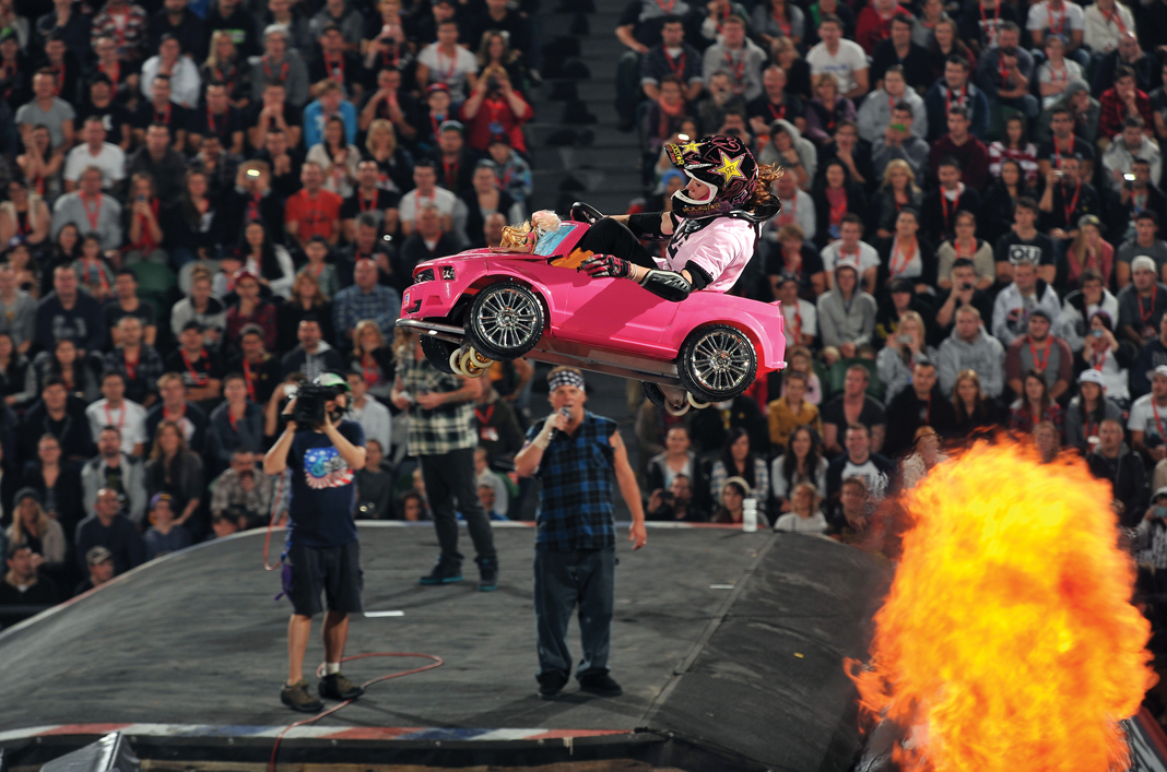 Travis Pastrana of Nitro Circus performing a stunt in a little pink car.