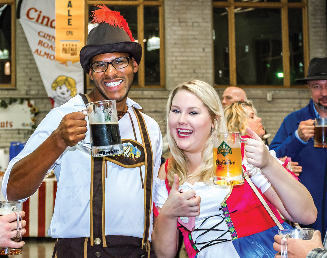 Two people dressed up in costume and holding mugs of beer at Twin Cities Oktoberfest.