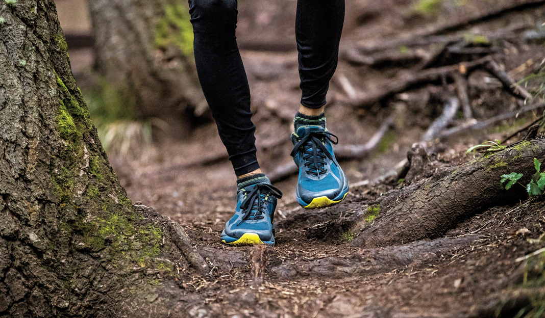 A pair of Vasque Trailbender II Trail-Running Shoes on the feet of someone walking on a trail.