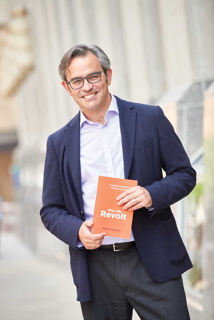 A portrait of Doctor Victor Montori holding his book Why We Revolt.