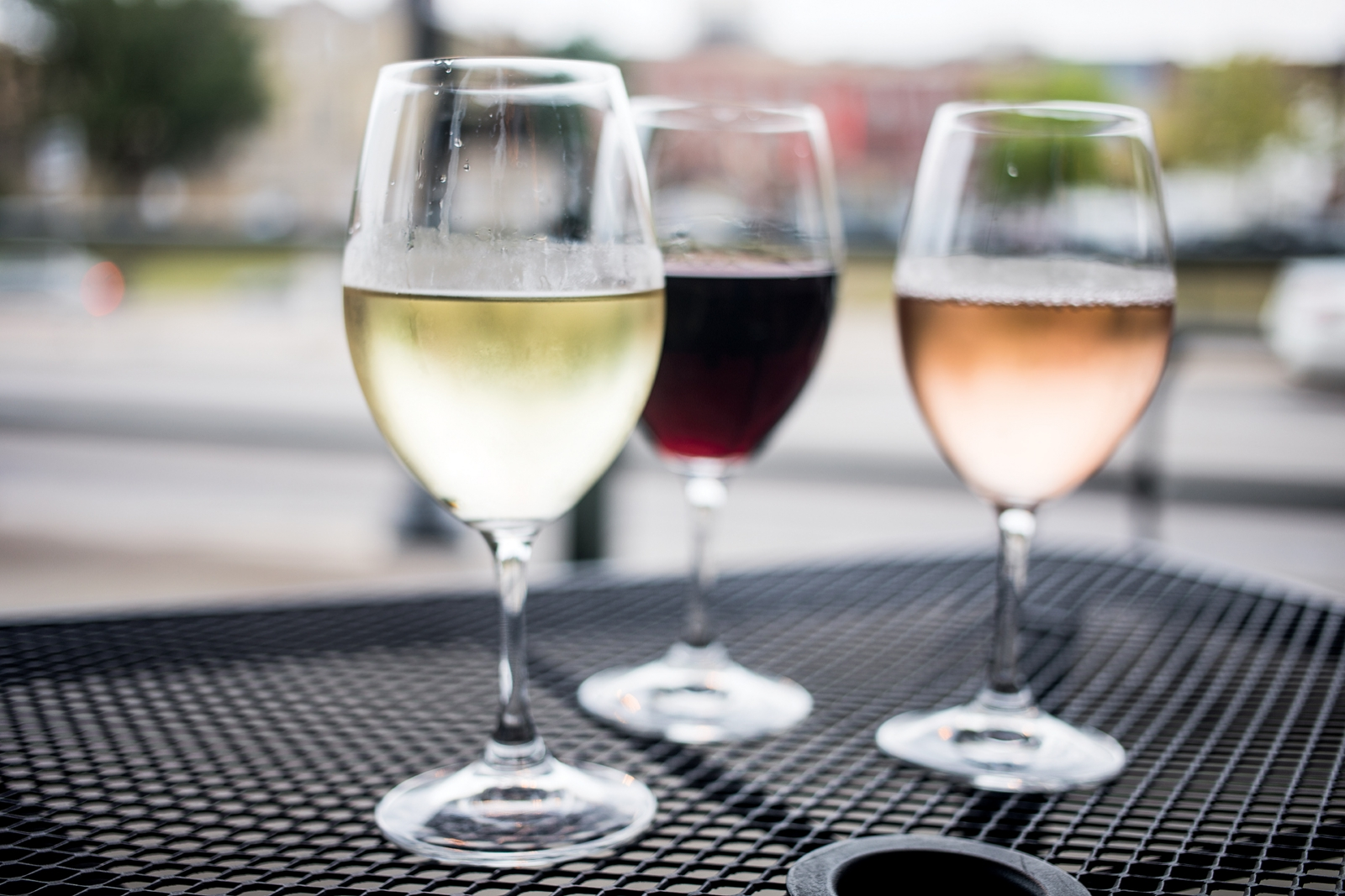 Three glasses of wine sitting on an outdoor table.