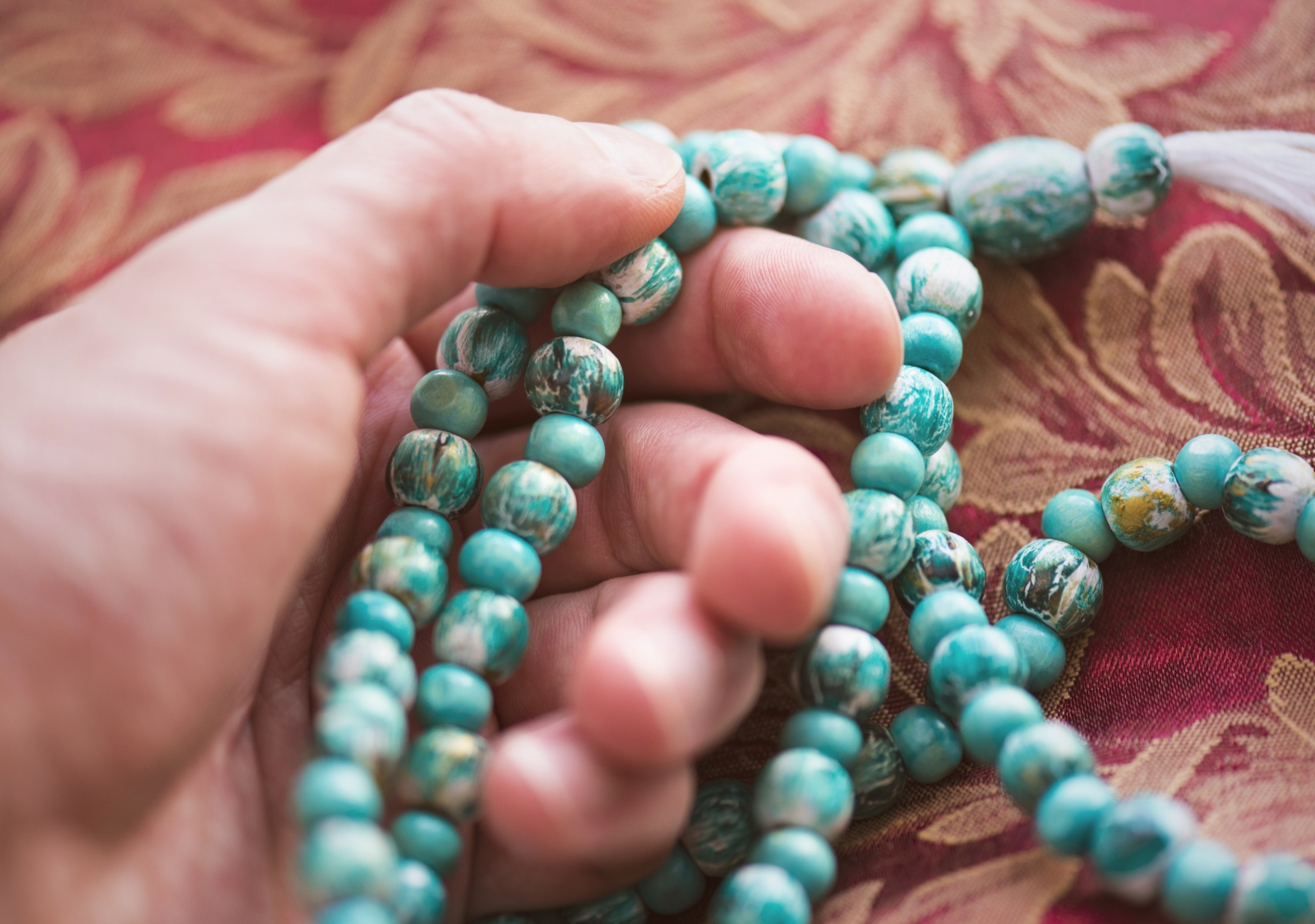 A man holding a turquoise male necklace. Photo by Savvapanf Photo (c) / Fotolia.