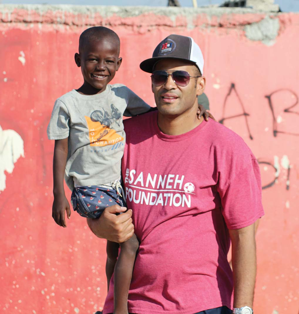 Tony Sanneh holding a child.