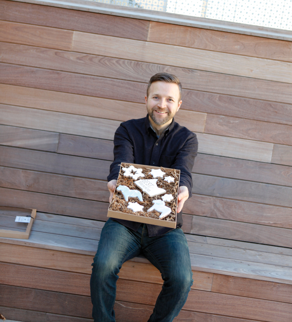 Minnesota Monthly editor Reed Fischer holding a box of cookies from The Cookie Creative.