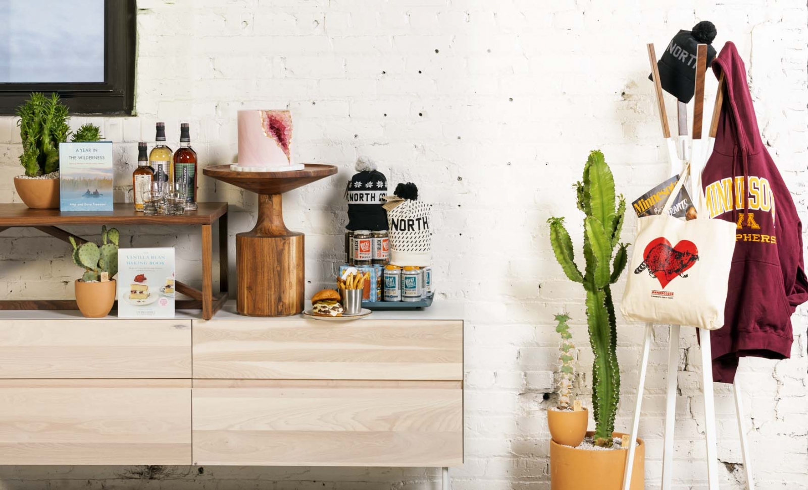 A room with a shelf full of items next to a potted cactus and a sweatshirt and bag hanging from a hanger.
