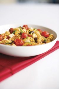 A bowl of pasta with sautéed cherry tomatoes, basil, and fresh mozzarella