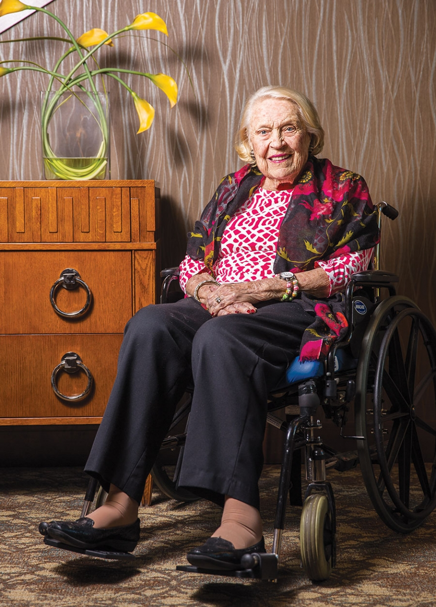 A portrait of Sally Pillsbury sitting next to a dresser with a vase of yellow flowers perched on top.