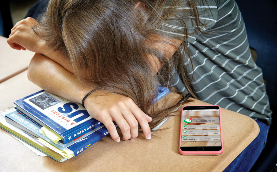 A girl has her head down on her desk and books with her phone laying next to her displaying 79 unread messages.