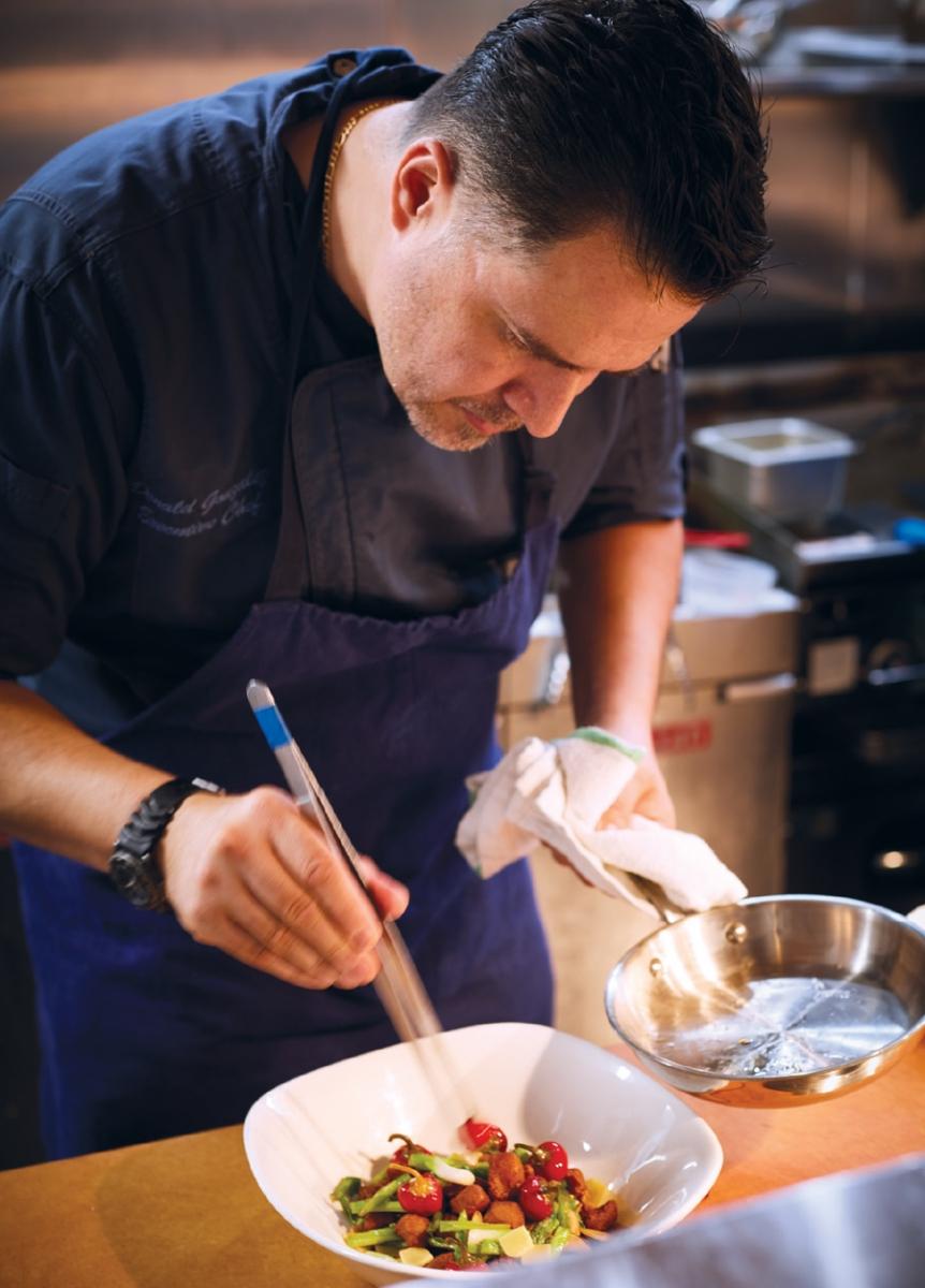 Chef Don Gonzalez at Gray Duck Tavern preparing a dish,