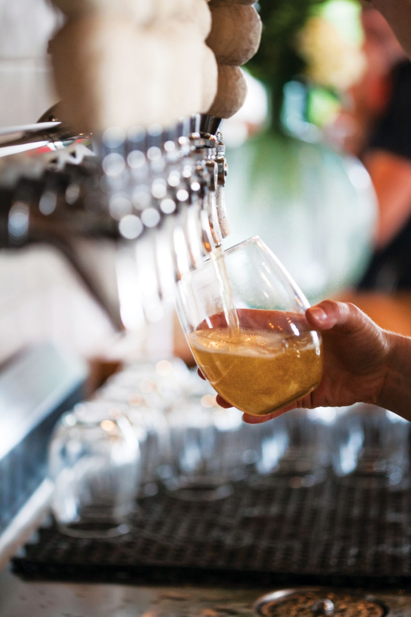Cider being dispensed from a tap into a glass.